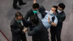 हांगकांग में चीनी राष्ट्रगान विधेयक पर चर्चा के दौरान दो सांसदों को बाहर निकाला
