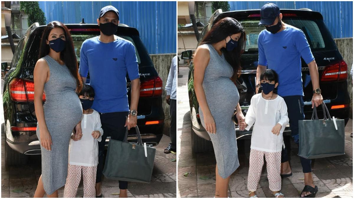 Harbhajan Singh holding bag of pregnant wife Geeta Basra, flaunts her baby bump in a dress: क्रिकेटर हरभजन सिंह (Harbhajan Singh) की खूबसूरत बीवी गीता बसरा (Geeta Basra) बहुत जल्द दूसरे बच्चे को जन्म देने वाली है। इन दिनों अदाकारा प्रेग्नेंसी पीरियड एंजॉय कर रही हैं। ऐसे में गीता बसरा को पति हरभजन के साथ मुंबई के खार इलाके में स्थित एक क्लिनिक के बाहर स्पॉट किया गया। इस दौरान गीता चेकअप के लिए क्लिनिक पहुंची थी। हरभजन और गीता के साथ इस दौरान उनकी बेटी हिनाया हीर प्लाहा (Hinaya Heer Plaha) दिखाई दी। क्लिनिक के बाहर गीता  टाइट सी ग्रे कलर की स्लीवलैस ड्रेस में बेबी बंप फ्लॉन्ट करती दिखाई दी। वहीं हरभजन सिंह ब्लू कलर की कैजुअल टी शर्ट और सिर पर कैप लगाएं नजर आए। इस दौरान यह सभी एक दूसरे के साथ काफी खुश दिखाई दे रहे थे। इन्होने मीडिया कैमरा को पोज देते हुए अपनी खूब तस्वीरें भी खिंचवाई। आप भी देखें भज्जी पाजी के परिवार की ये फोटोज... (फोटो साभार- @ Instagram)